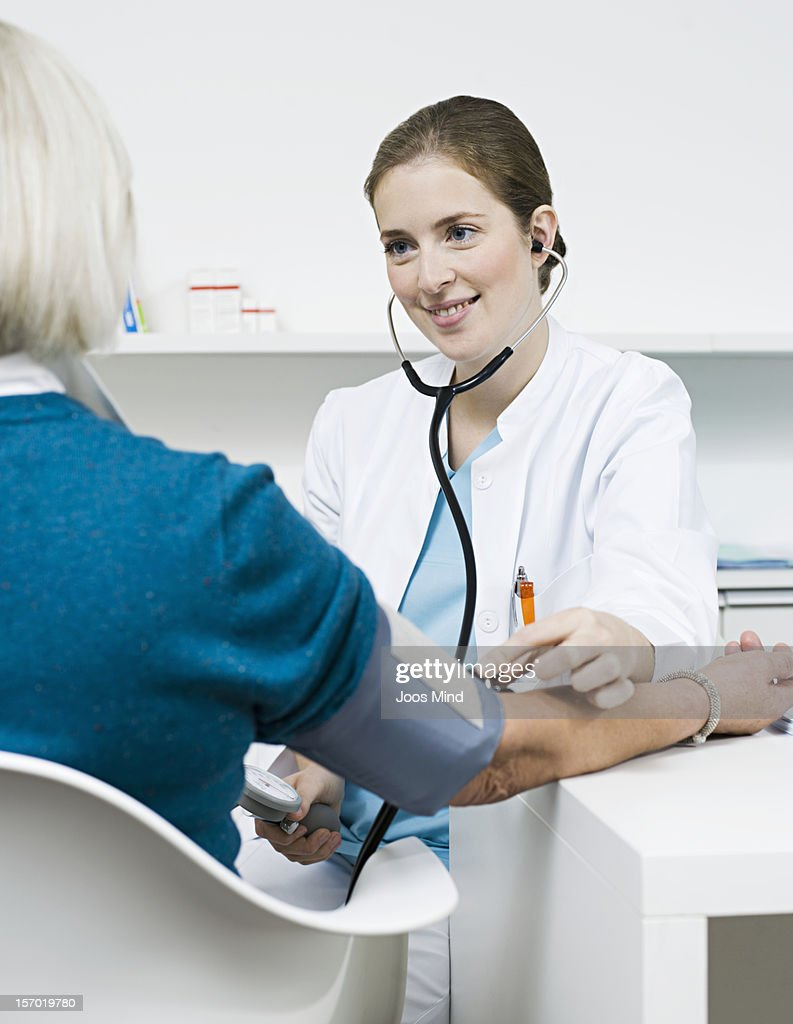 doctor checking patients blood pressure, smiling