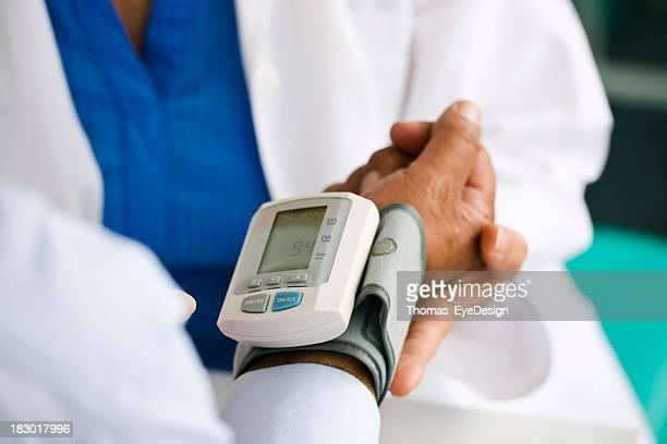 Arzt prüfen den Blutdruck von Patienten Ihrer