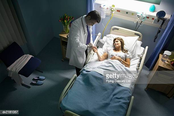 Doctor Checking the Time and Standing Next to a Female Patient Lying in a Hospital Bed at Night
