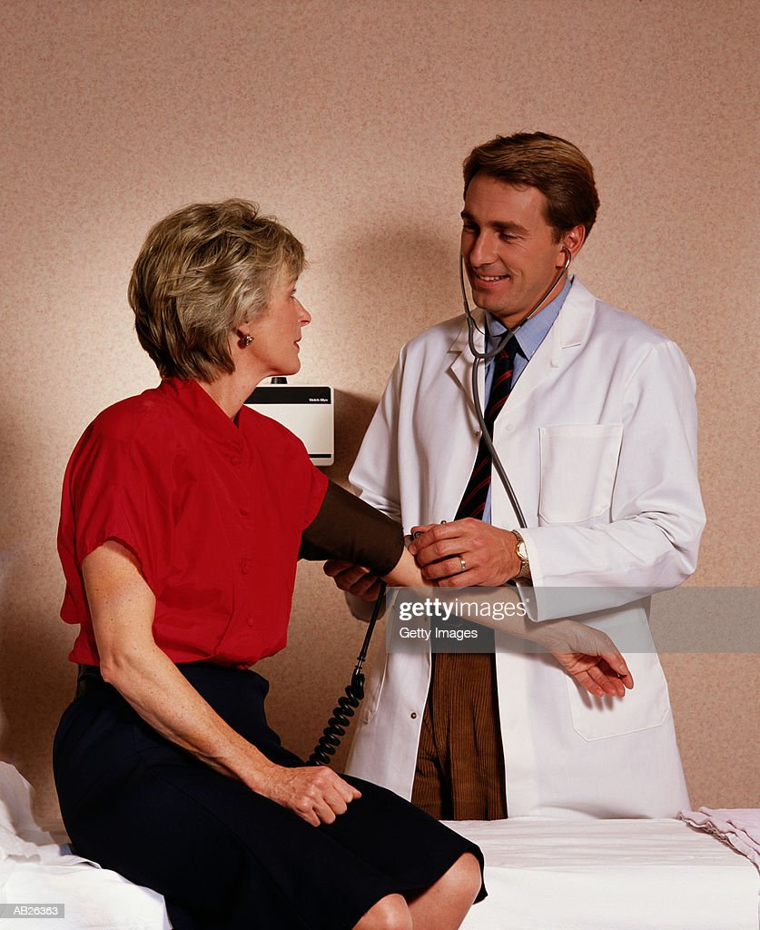 Doctor checking woman's blood pressure : Stock Photo