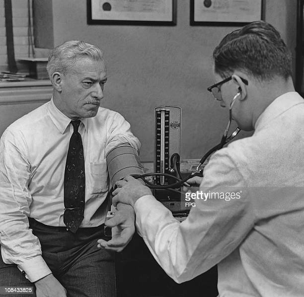 A doctor checks a man's blood pressure with a sphygmomanometer during a medical examination in the 1950's