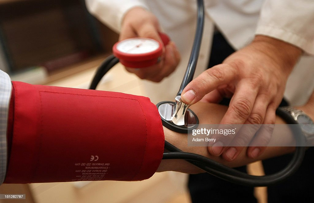 A doctor checks a patient's blood pressure on September 5, 2012 in Berlin, Germany. Doctors in the country are demanding higher payments from health insurance companies (Krankenkassen). Over 20 doctors' associations are expected to hold a vote this week over possible strikes and temporary closings of their practices if assurances that a requested additional annual increase of 3.5 billion euros (4,390,475,550 USD) in payments are not provided. The Kassenaerztlichen Bundesvereinigung (KBV), the National Association of Statutory Health Insurance Physicians, unexpectedly broke off talks with the health insurance companies on Monday.