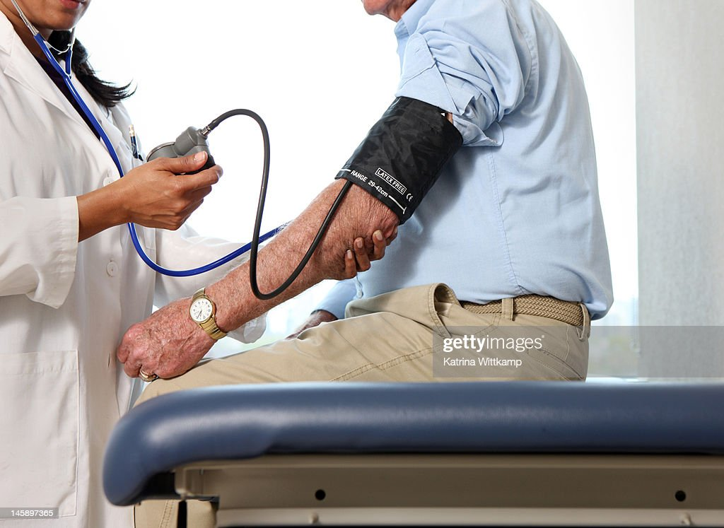 Doctor checks man's blood pressure. : Stock Photo
