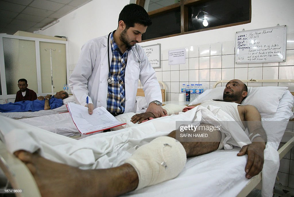 A doctor checks on a wounded Iraqi man resting at a hospital in the northern Iraqi city of Arbil on April 25, 2013 after he was injured during violent clashes between security forces and Sunni Arab protesters and their supporters in Hawijah. Iraqi Prime Minister Nuri al-Maliki warned of attempts to return the country to 'sectarian civil war,' as a wave of violence killed more than 140 people over three days. AFP PHOTO / SAFIN HAMED