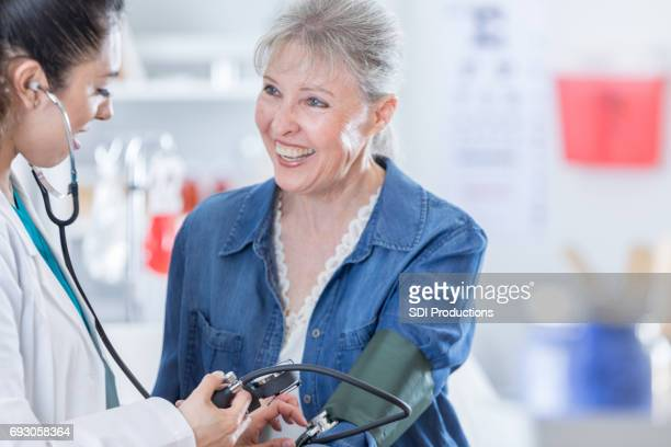 Arzt überprüft Blutdruck ältere Patienten