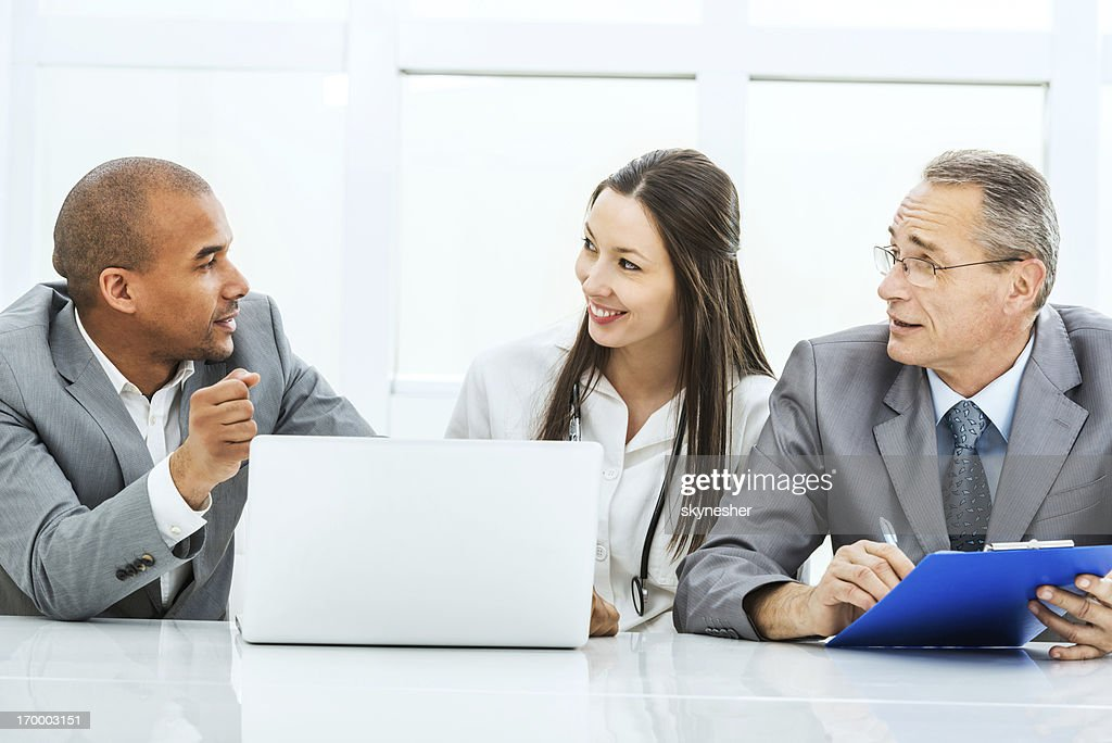 Doctor collaborating with a business team. : Stock Photo