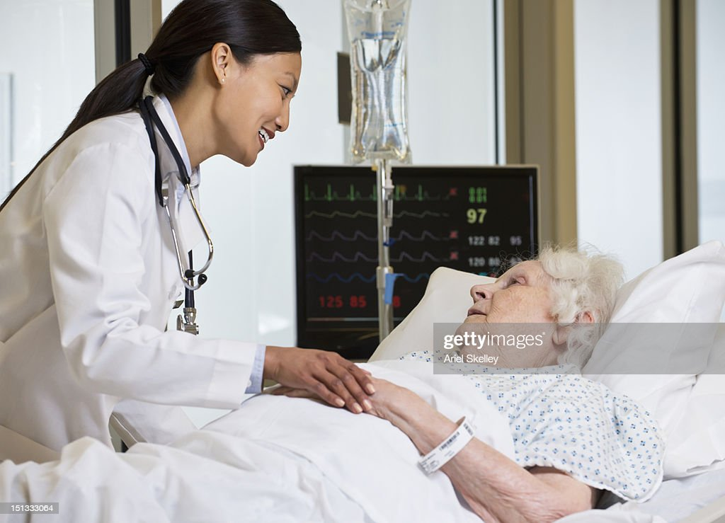 Doctor comforting patient in hospital : Stock Photo