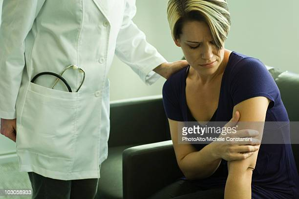 Doctor comforting woman in the waiting room