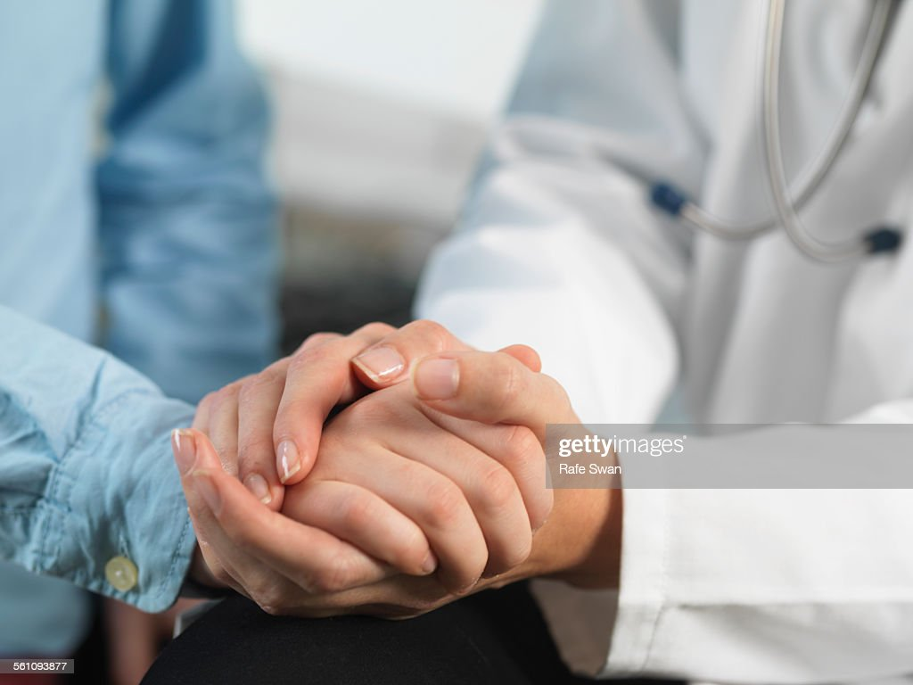 Doctor comforting young boy in clinic