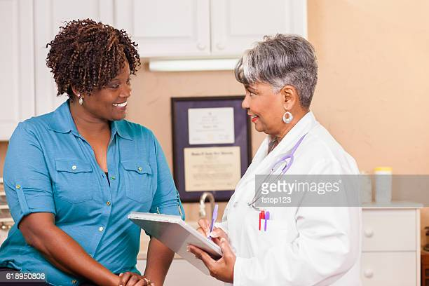 Doctor conducts medical consultation with adult patient at clinic.