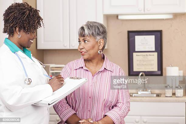 Doctor conducts medical consultation with senior adult patient at clinic.