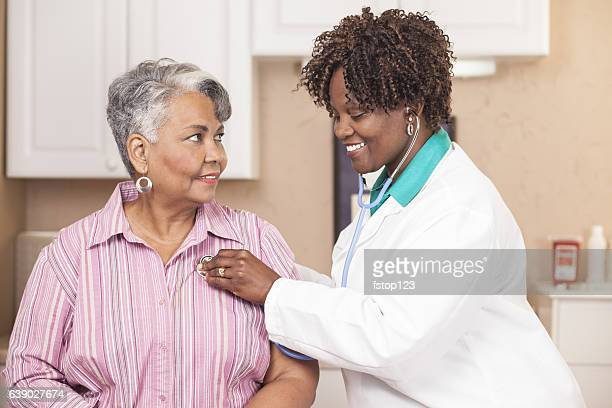 Doctor conducts medical exam on senior adult patient at clinic.