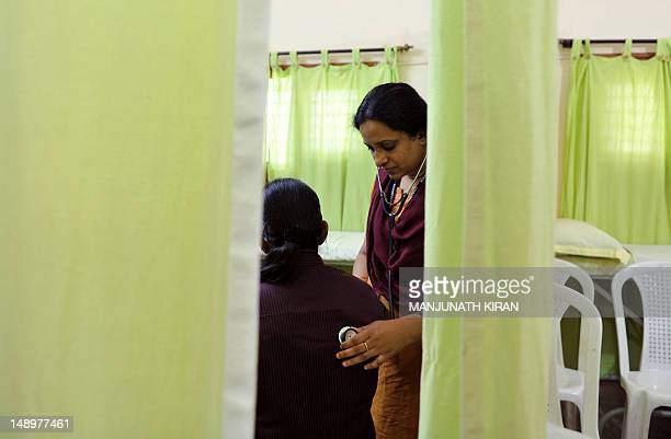 A doctor conducts routine tests on an HIVpositive patient at the Anti Retroviral Therapy clinic at the Asha Foundation a charitable and voluntary...