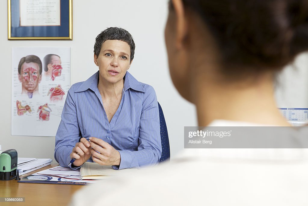 Doctor consulting with patient : Stock Photo