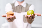 Doctor a dentist a man holds a green apple and a sweet cupcake and shows on the scales a choice of useful against harmful