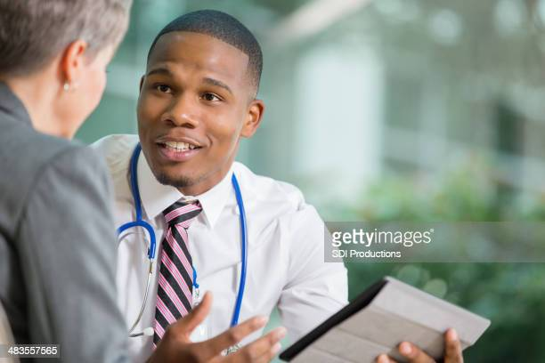 Doctor discussing hospital policy changes with senior patient in office