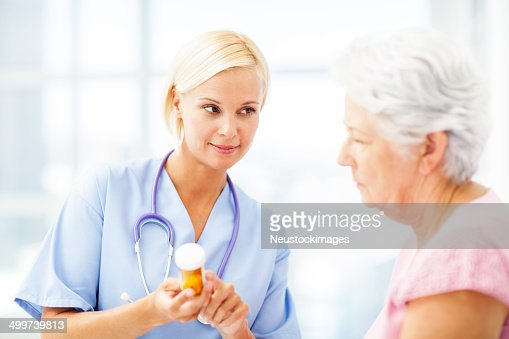 Doctor Discussing Medication With Female Patient In Hospital