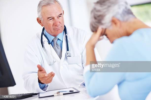 Médico a discutir relatórios com infeliz doente