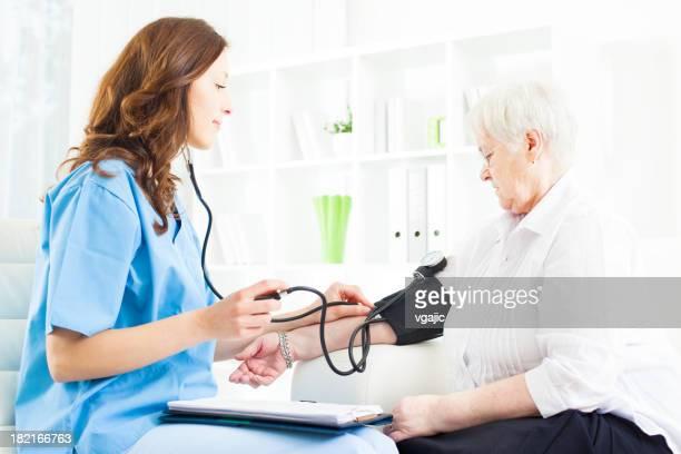 Arzt macht Blutdruck überprüfen Senior Frau.