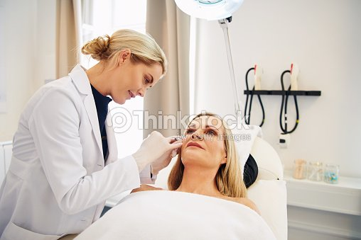 Doctor doing botox injections on a mature client's face : Stock Photo