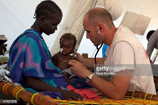 Doctor Emmanuel Berbain examines a young patient as medical staff look on at the MSF hospital at the Yida refugee camp along the border with North...
