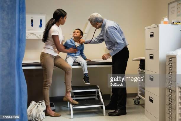 Arzt untersucht einen kleiner Junge