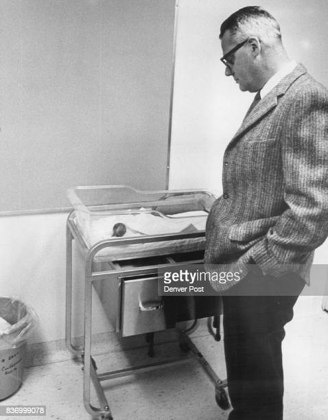 Doctor Examines Plastic Bassinet Which Had Contained Unnamed Baby He's Dr George S Tyner associate dean of medicine and head of hospital operations...