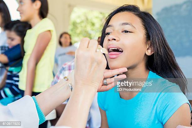 Doctor examines preteen girl at outdoor clinic