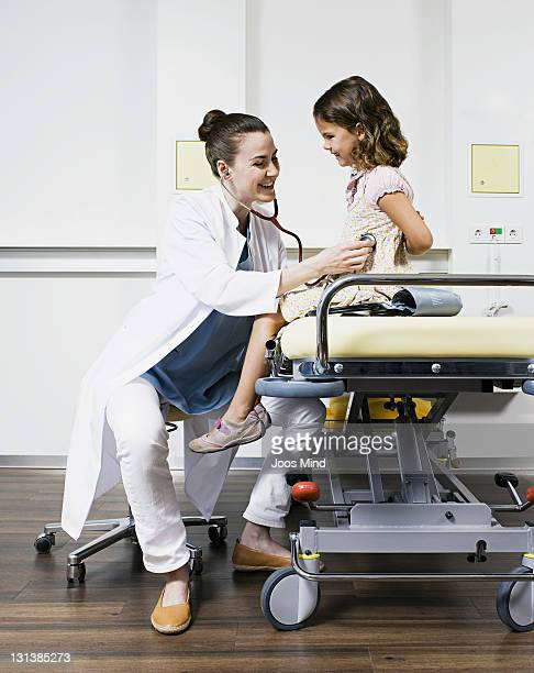 doctor examing child using stethoscope, laughing
