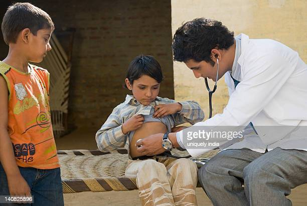 Doctor examining a boy with a stethoscope, Hasanpur, Haryana, India