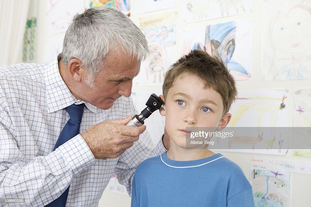 Doctor examining a boy's ear : Stock Photo