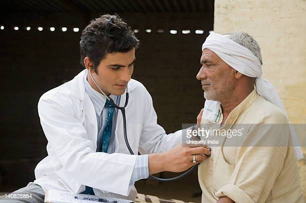Doctor examining a farmer with a stethoscope, Hasanpur, Haryana, India