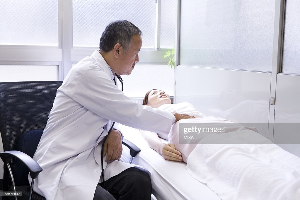 Doctor examining a patient : Stock Photo