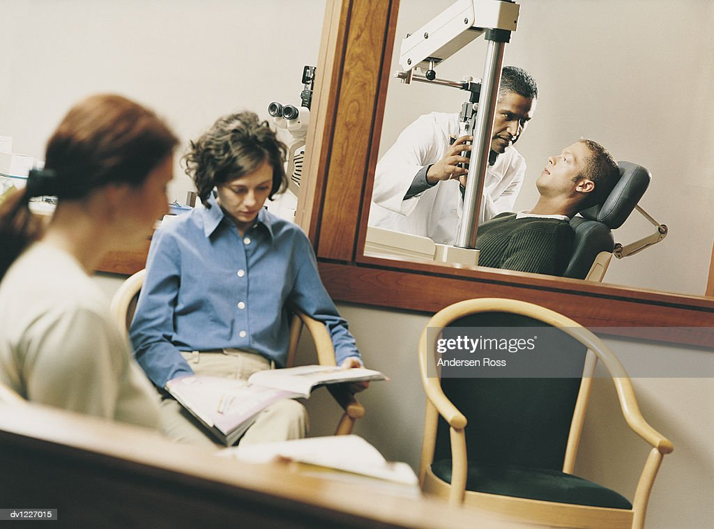 Doctor Examining a Patient Using Medical Technical Equipment Behind a Waiting Room : Stock Photo