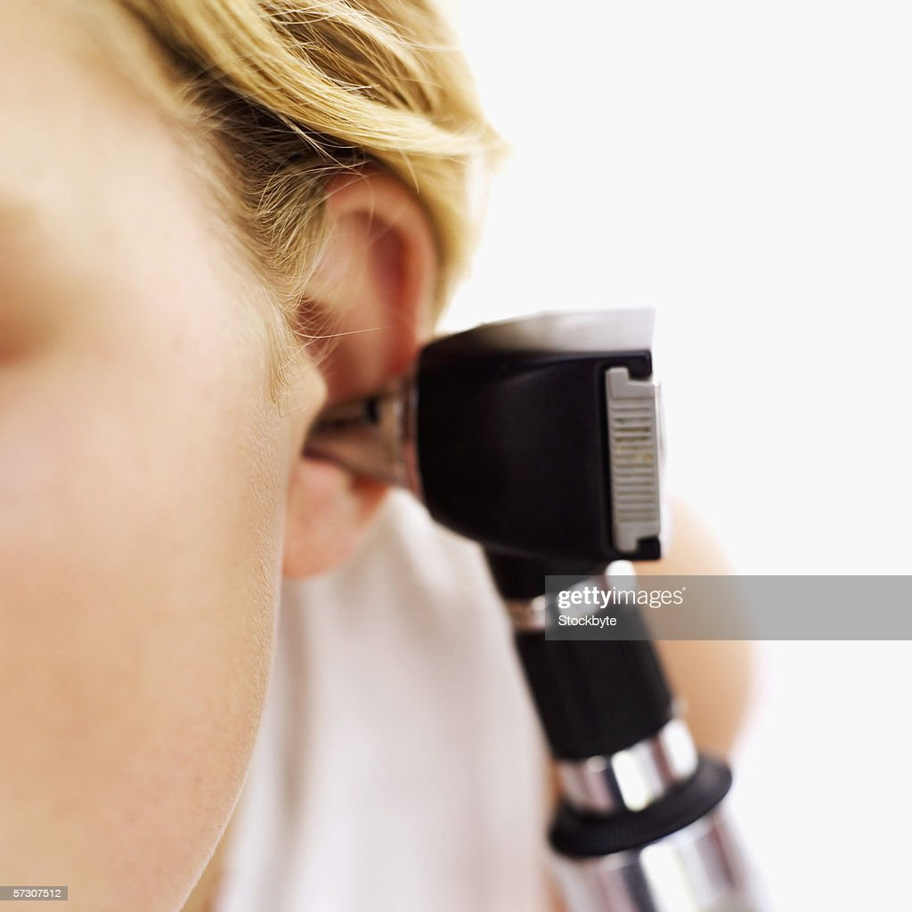 Doctor examining a person's ear using an otoscope : Stock Photo
