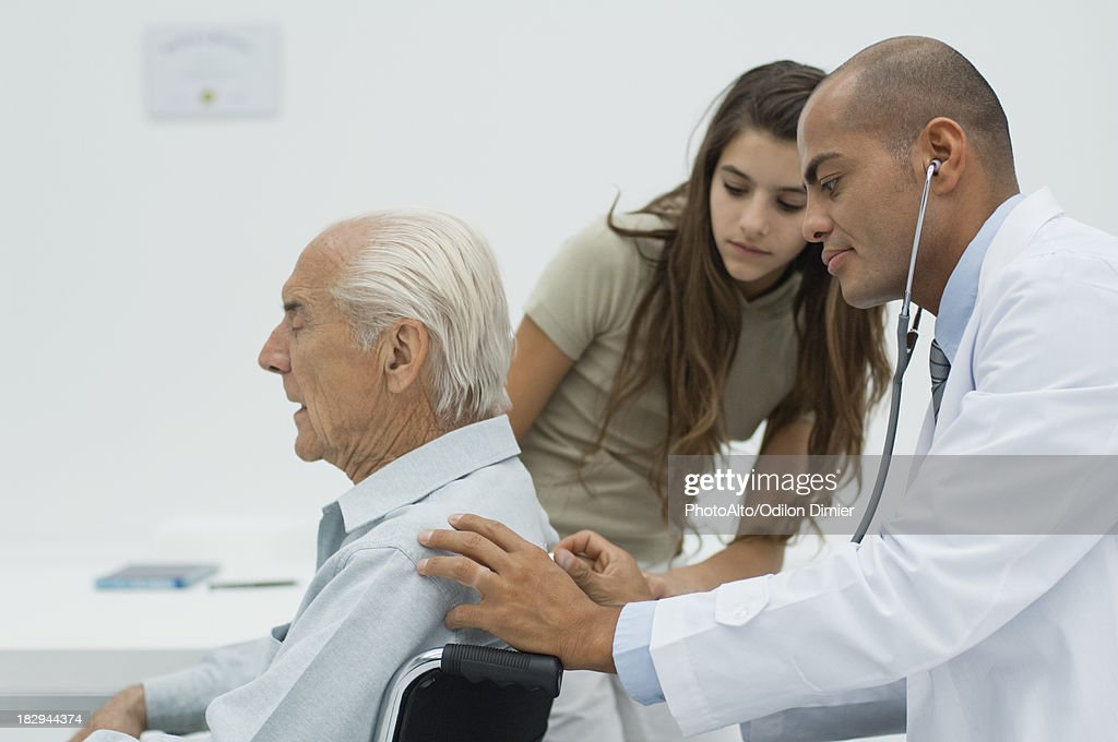 Doctor examining elderly patient with stethoscope : Stock Photo