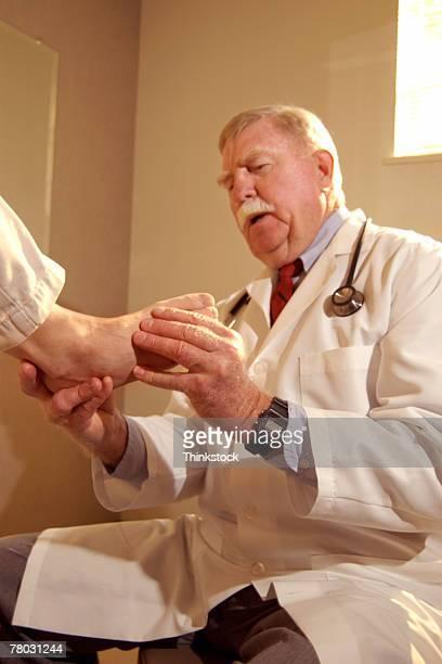 Doctor examining foot of patient