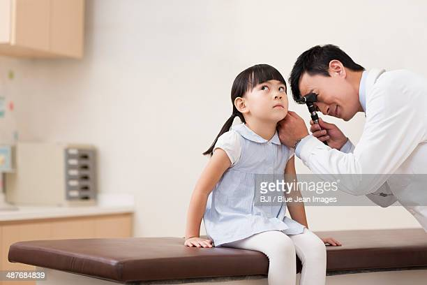 Doctor examining girl's ears