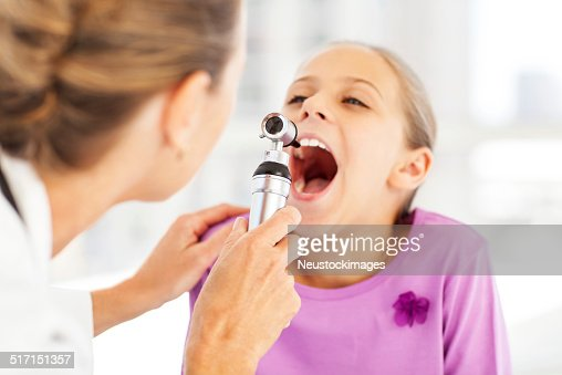Doctor Examining Girl's Throat With Otoscope In Clinic