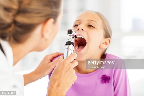 医師調べる女の子ののどにオトスコープのクリニック