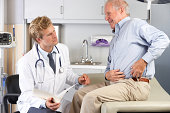 Male Doctor Examining Male senior Patient With Hip Pain