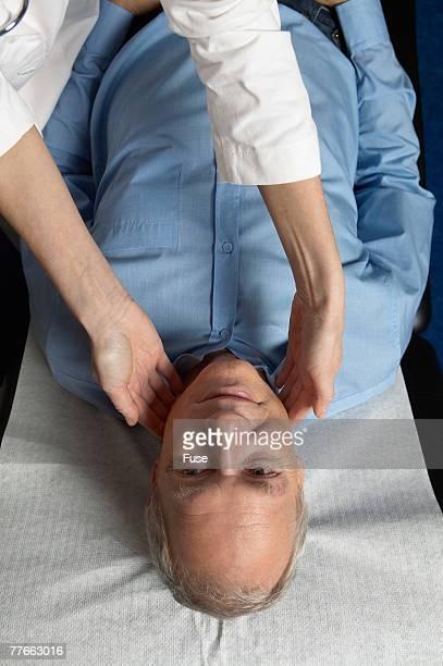 Doctor Examining Mans Lymph Nodes