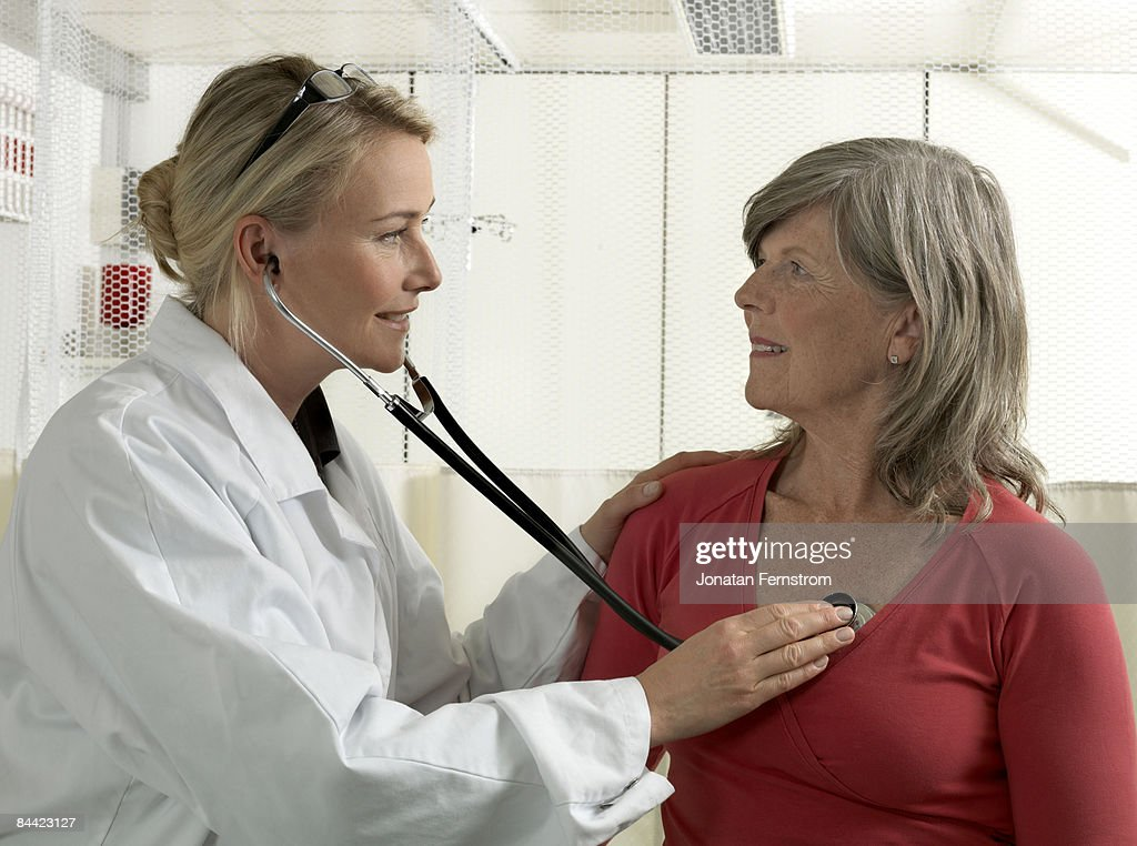Doctor examining mature woman : Stock Photo
