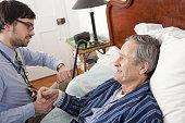 Doctor examining older man at home