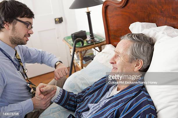 Doctor examining older man at home