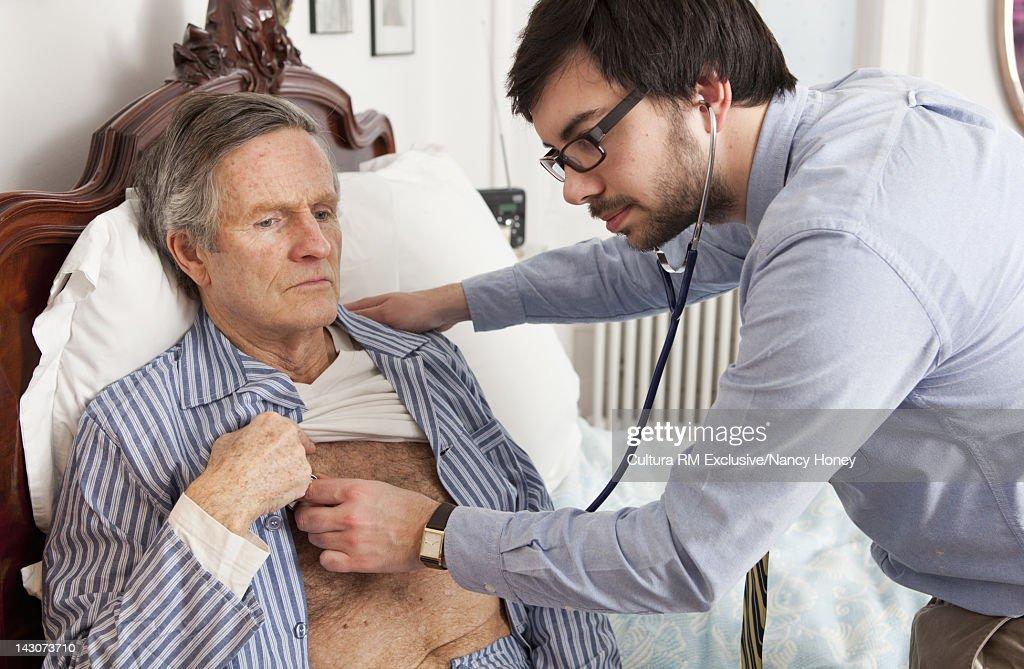 Doctor examining older man at home : Stock Photo