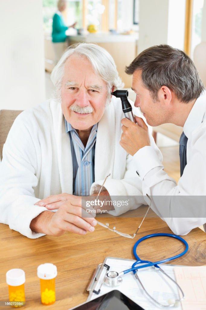 Doctor examining older man's ear at house call