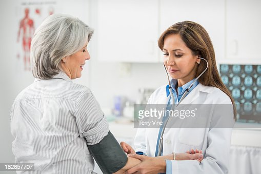 Doctor examining patient in office : Stock Photo