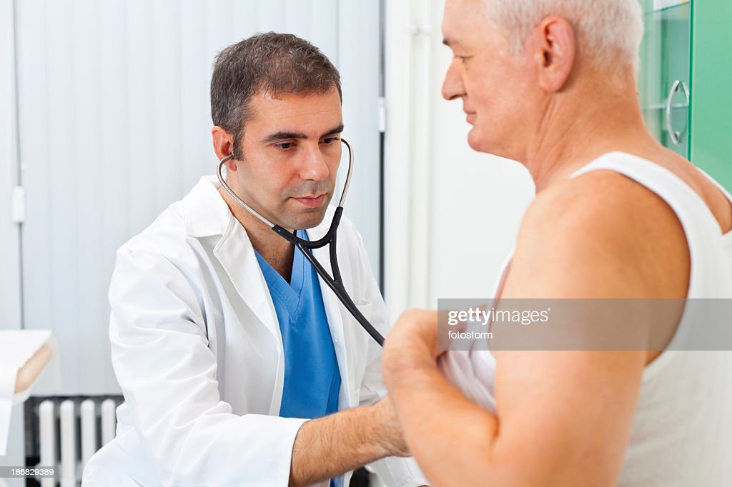Doctor examining patient with stethoscope : Stock Photo
