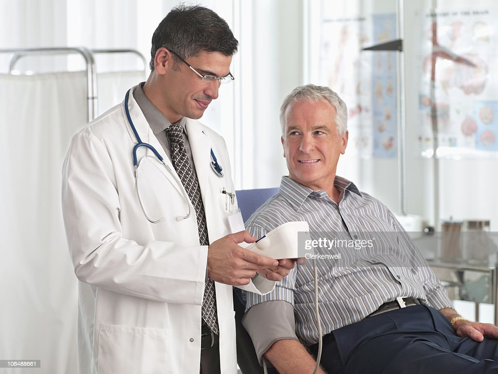 Doctor examining patient's blood pressure, at hospital : Stock Photo